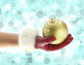 Woman's hand with red glove holding a Christmas ball — Stock Photo