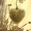 Stock Photo: Christmas love. Heart ornament hanging on a branch