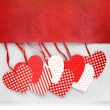 Heart ornaments hanging on fabric background — Stock Photo