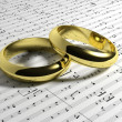 Wedding rings on music notes background  — Stock Photo