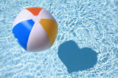 Summer love, Beach Ball on the swimming Pool with heart shaped shadow — Stock Photo