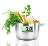 Fresh vegetables in a casserole pot with digital weight scale — Stock Photo