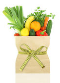 Fresh vegetables and fruits in a paper grocery bag with measuring tape — Stok fotoğraf