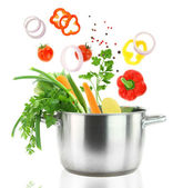 Fresh vegetables falling into a stainless steel casserole pot — Stock Photo