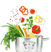 Fresh vegetables falling into a casserole pot with weight scale — Stock Photo