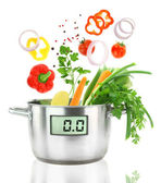 Fresh vegetables falling into a casserole pot with digital weight scale — Stock Photo