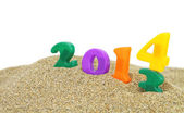 Multicolored new year 2014 on the sand — Stock Photo