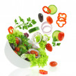 Fresh mixed vegetables falling into a bowl of salad - Stockfoto