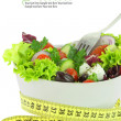 Diet meal. Vegetables salad in a bowl with measuring tape — Stock Photo #22563443