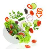 落入一碗沙拉新鲜混合的蔬菜新鮮な野菜と白で隔離されるシルバー フォーク — 图库照片