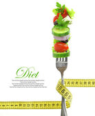 Fresh mixed vegetables on fork with measuring tape — Stock Photo