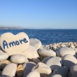 Amore written on heart shaped stone on the beach — Stock Photo #23287014