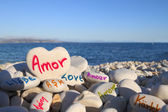 Love written in different languages, on the beach — Stock Photo