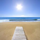 Wooden floor on golden sandy beach — Stock Photo