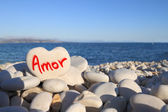 Amor written on heart shaped stone on the beach — Zdjęcie stockowe