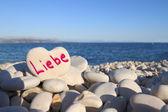Liebe written on heart shaped stone on the beach — Stock Photo