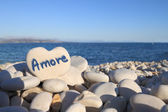 Amore written on heart shaped stone on the beach — Stock Photo