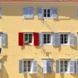 Stand out from the crowd - Being different concept, Red shutter among grey shutters — Stock Photo