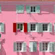Pink building with a red shutter among grey shutters — Stock Photo #23465060