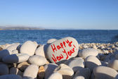 Happy new year written on heart shaped stone on the beach with spray brush — Stock Photo