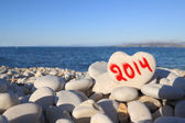 2014 new year written on heart shaped stone on the beach with spray brush — Zdjęcie stockowe