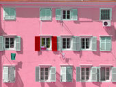 Pink building with a red shutter among grey shutters — Stock Photo