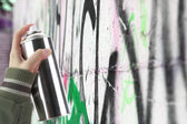 Human hand holding a graffiti Spray can in front of a colorful wall — Stock Photo