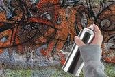 落書きスプレーを持っている人間手カラフルな壁の前にすることができます。 — ストック写真