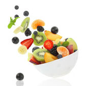 Fresh fruits coming out from a bowl — Stock Photo