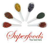 Superfoods in porcelain spoons. Pollen, goji berries, blueberries, spirulina, Hippophae and saffron — Stock Photo
