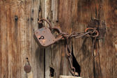 Old rusty padlock with chain on wooden door — Stock Photo