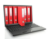 Laptop with red ring binders — Stock Photo