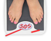 Woman' s feet on bathroom scale — Stock Photo