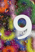 Number nine on abstract colorful drops background — Stock Photo