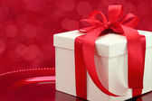 Gift box on a plate with elegant red lights background — Stock Photo
