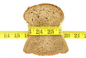 Wholesome slice of bread with measuring tape isolated on white — Stock fotografie
