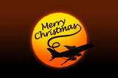 Sunset background with silhouette of airplane and greeting Christmas text — Stock Photo