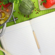 Blank recipe book with vegetable soup, kitchen equipment and veggies around them — Stock Photo #32576181