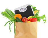Fresh groceries in a paper bag with weight scale — Stock Photo