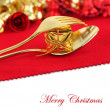 Christmas golden cutlery with ornament on red background — Stock Photo