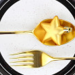 Christmas golden cutlery on a plate — Stock Photo