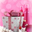 Stock Photo: Christmas presents, beauty products with snow and pink background