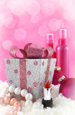 Christmas presents, beauty products with snow and pink background — Stock Photo