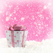 Present box with snow and pink background — Zdjęcie stockowe