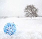 Blue Christmas ball with snowfield as background — Stock Photo