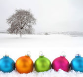 Colorful Christmas balls with snowfield as background — Stock Photo