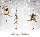 Christmas wooden ornaments hanging on snowy branch — Stock Photo