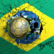 Gold soccer ball breaking though wall with Brazilian flag — Stock Photo