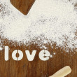 "Stencil word ""love"" made with flour on wooden table — Stockfoto"