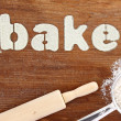 "Stencil word ""bake"" made with flour on wooden table — Stockfoto"
